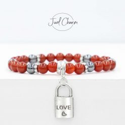 Handmade red Carnelian and Hematite gemstone bracelet shown with a love lock charm