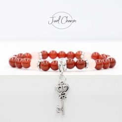 Handmade red Carnelian and Rose Quartz gemstone bracelet shown with a heart key charm