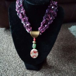 Hand knitted cowl with hanging pendant