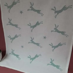 Handprinted leaping hare design tea towel in duck egg blue.