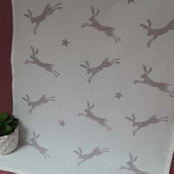 Handprinted leaping hare design tea towel in dusky pink.
