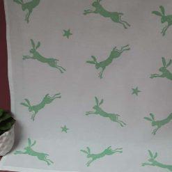 Handprinted leaping hare design tea towel in pastel green.