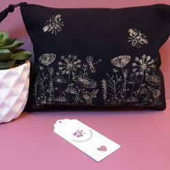 Handprinted black cotton make-up bag with flower meadow design.