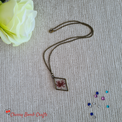 Bronze resin diamond shaped pendant with red flower setting