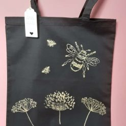 Handprinted black and gold cotton tote bag with long handles.