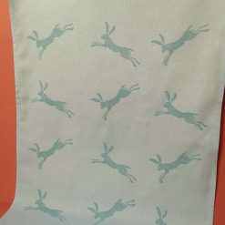 Handprinted blue cotton tea towel with leaping hare design.