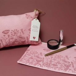 Handprinted pink cotton make-up bag with flower meadow design.
