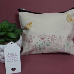 Handprinted natural cotton make-up bag with flower meadow design.