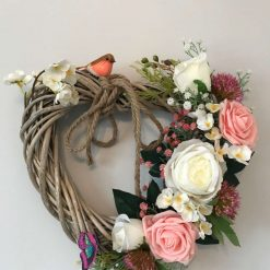 Wicker heart wreath with beautiful white and pink roses and a little robin