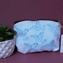 Handprinted cotton makeup bag with blue flying bird design.