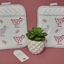 Handprinted kitchen pot holder with pink/raspberry chicken design.