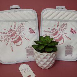 Handprinted kitchen pot holder with pink/raspberry bee design.