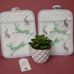 Handprinted kitchen pot holder with pink/green hare design.