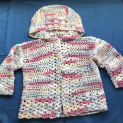 Baby girl crochet cardigan in variegated pink yarn. Second size
