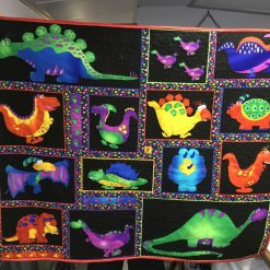 Dinosaur quilt. Bright coloured dinosaur fabric. Can be used as a floor quilt or on a cot.