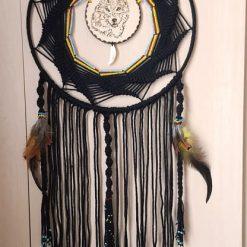 Handmade macrame dream catcher with a Native American motif.